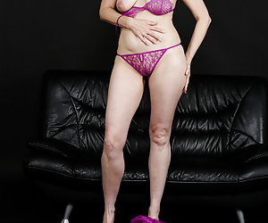 Posing in front of the camera in purple lingerie and negligee.And a strip, of course.