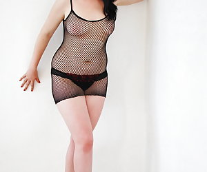 Mona Summers, sexy young Dutch pornstar dressed in black fishnet dress and high heel shoes.
