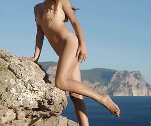 Smiling young hottie sunning her nude body at the sea-side