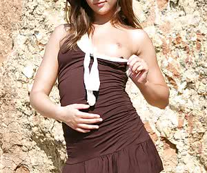 Teenie taking off her brown clothes and posing at the rocks in only her stockings